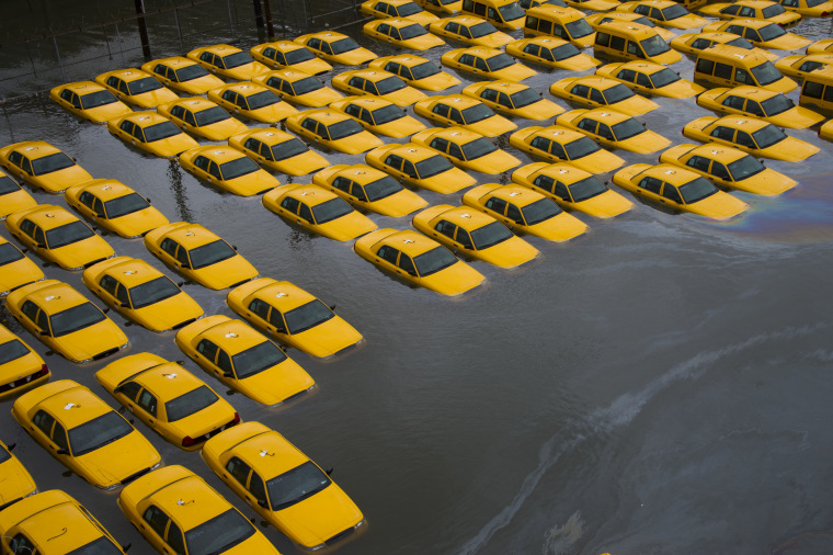 A parking lot full of yellow cabs is flooded as a result of Hurricane Sandy in Hoboken, NJ. (AP Photo/Charles Sykes)