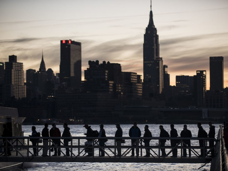 People board the NY Waterways ferry with the Manhattan skyline in the background (AFP PHOTO/Brendan Smialowski)