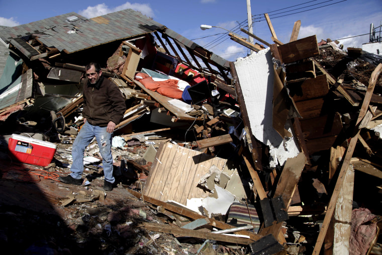 James Traina climbs over the remains of his parent's house which was destroyed by Superstorm Sandy in Staten Island, N.Y. Friday, Nov. 2, 2012. (AP Photo/Seth Wenig)