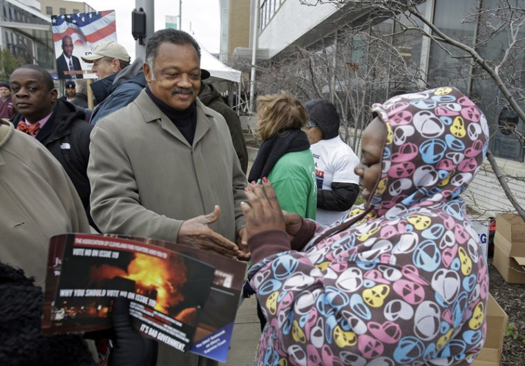 Rev. Jesse Jackson greets voters waiting in line at the Cuyahoga County Board of Elections in Cleveland on the final day of early voting Monday, Nov. 5. About 1.6 million people have already voted early in Ohio. (AP Photo/Mark Duncan)
