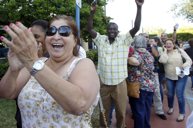 Myrna Peralta, left, and other voters react after the elections office in Miami-Dade County reopened its doors to voters who waited in long lines for an absentee ballot in Doral, Fla., Sunday, Nov. 4. The doors were closed after election officials were...