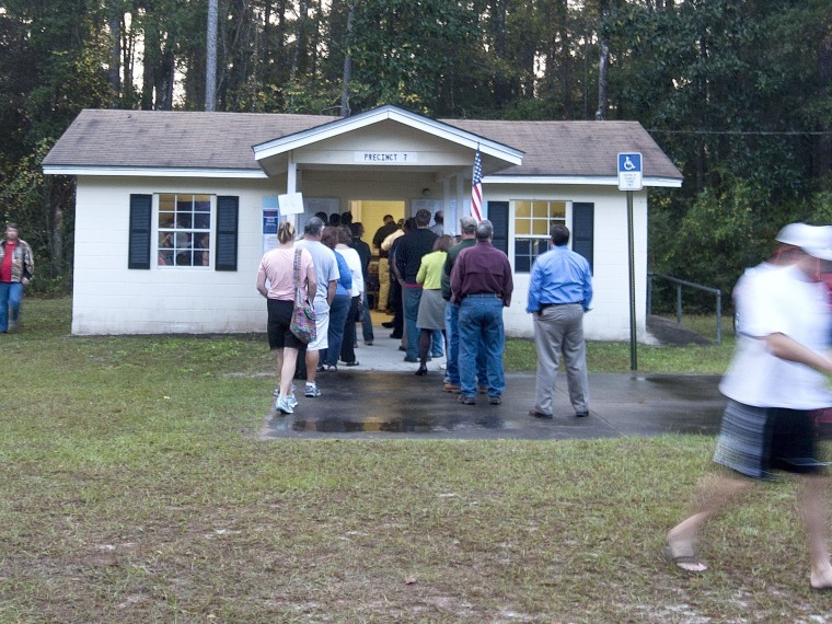 Voters leave the polls just after dawn as other voters queue to place their ballots at the tiny County Polling House in the Ivan Community of Wakulla County on November 6, 2012 in Crawfordville, Florida. The swing state of Florida is recognised to be...