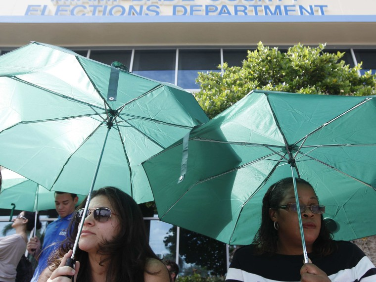 Yaine Noguera (L) and Sheron Reid wait in line to obtain and deposit their absentee ballots at the Miami-Dade County Elections Department Headquarters on the final day before Election Day, in Doral, Florida November 5, 2012. (Photo by  REUTERS/Andrew...