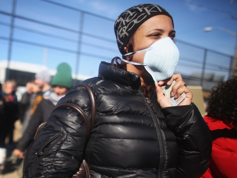Rockaway resident Saajida O'Quinn wears a protective mask as she prepares to vote in a makeshift tent set up as a polling place at Scholars' Academy, PS 180, in the Rockaway neighborhood on November 6, 2012 in the Queens borough of New York City. The...