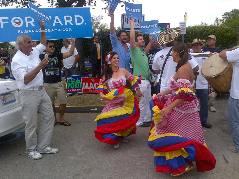 Dancers perform as more than 250 people line up outside the Miami-Dade elections headquarters in Doral, Florida, on November 5, 2012 to cast absentee ballots in person, a day after a temporary shutdown at the site led to widespread confusion.   (Photo...