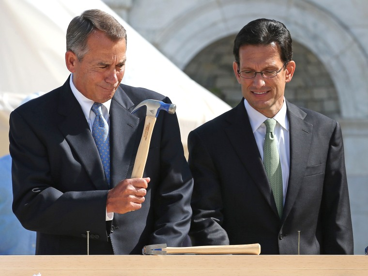 """FILE PHOTO:  Speaker of the House John Boehner (R-OH) (L) wields his hammer with House Majority Leader Eric Cantor (R-VA) before the """"First Nail"""" ceremony, signifying the start of construction of the 2013 Inaugural Platform on the West Front of the U.S..."""