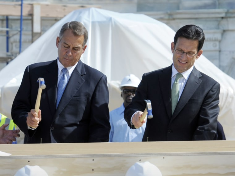 FILE PHOTO: Speaker of the House John Boehner, R-Ohio, left, House Majority Leader Eric Cantor, R-Va., right, hammer nails into a plank during the First Nail Ceremony for the official launch of construction of the Inaugural platform where the President...