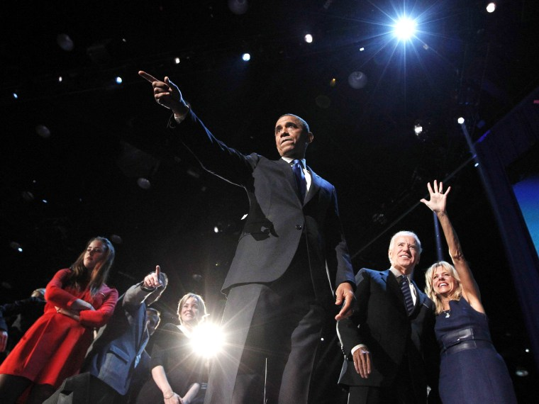 U.S. President Barack Obama gestures onstage during his election night victory rally in Chicago November 7, 2012. Beside Obama are Vice President Joe Biden (2nd R) and Biden's wife Jill Biden.    (Photo by REUTERS/Jason Reed)