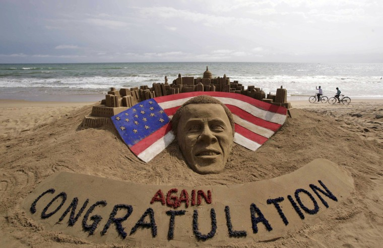 Cyclists ride on a beach passing by a sand sculpture congratulating U.S. president Barack Obama for a second term in office in Puri, India.(AP Photo/Biswaranjan Rout)