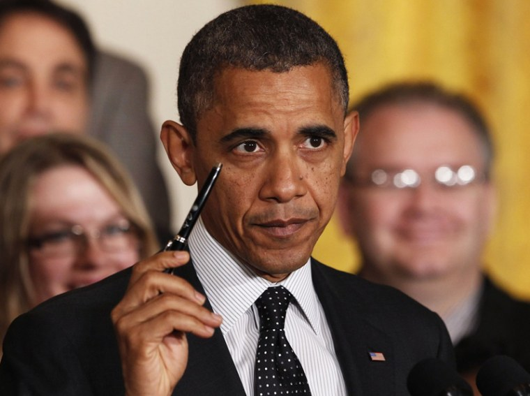 """President Barack Obama holds up a pen as he delivers a statement on the """"fiscal cliff"""" in the East Room of the White House in Washington, November 9. The president  he was ready to sign a bill """"right away"""" to extend the Bush tax cuts for the bottom 98%..."""