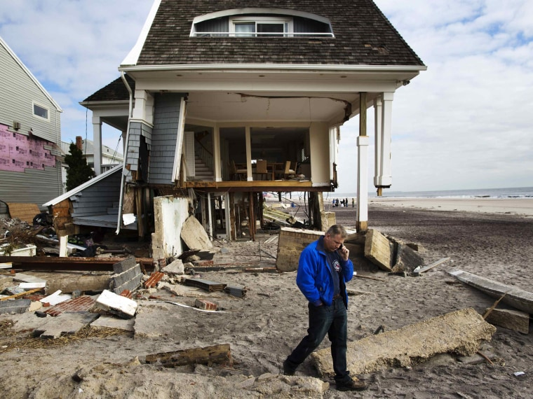 Homeowner Rob Ostrander talks on the phone in front of his Hurricane Sandy damaged home in the Brooklyn borough region of Belle Harbor in New York November 14, 2012.  (Photo by Lucas Jackson/Reuters)