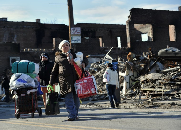 After getting household supplies from a nearby distribution center, people walk home past burned out businesses in the Rockaway Park section of Queens November 14, 2012 in New York as the city recovers from the effects of super storm Sandy. (AFP PHOTO...