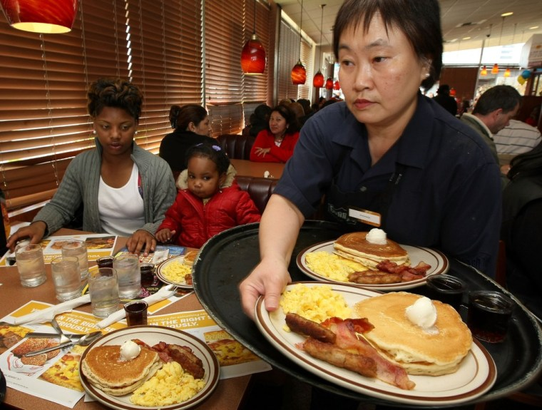 EMERYVILLE, CA - FEBRUARY 03:  Denny's waitress Fong Van Luben (R) delivers free Grand Slam breakfasts to customers February 3, 2009 in Emeryville, California. (Photo by Justin Sullivan/Getty Images)