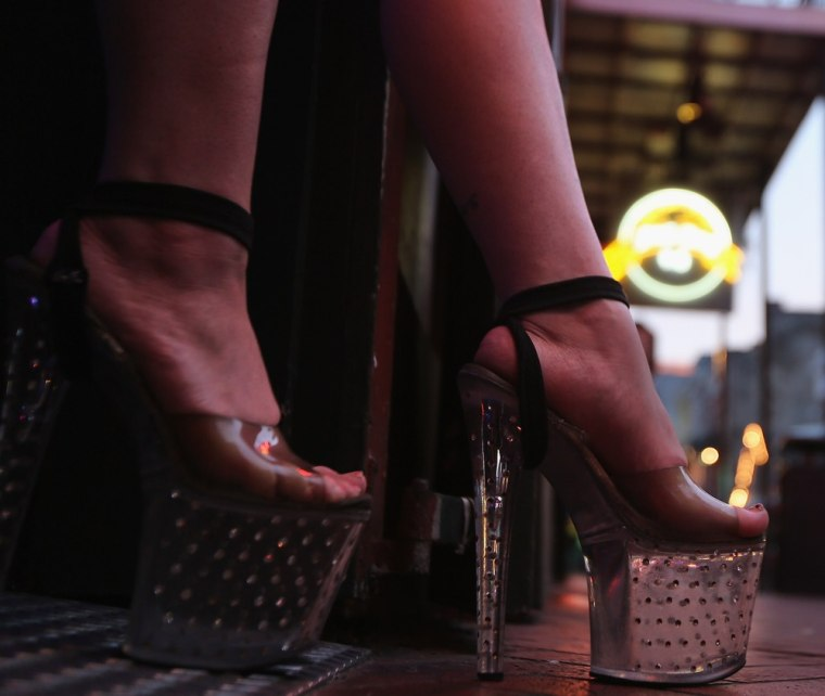 An exotic dancer stands at a club entrance on Bourbon Street on August 31, 2012 in the French Quarter of New Orleans, Louisiana. (Photo by John Moore/Getty Images)