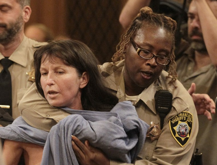 Protester Gypsy Taub is covered up by a San Francisco Sheriff after taking off her clothes at a Board of Supervisors meeting at City Hall in San Francisco, Tuesday, Nov. 20. San Francisco lawmakers on Tuesday narrowly approved a proposal to ban public...