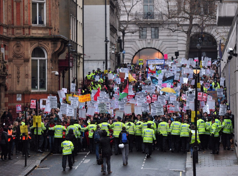 Police officers keep control during a student rally in central London on November 21, 2012 against sharp rises in university tuition fees, funding cuts and high youth unemployment. (AFP PHOTO/CARL COURT)