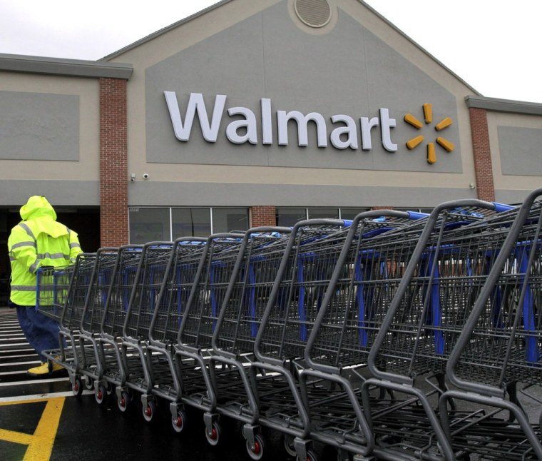 In this Tuesday, Nov. 13, 2012 photo a worker pulls a line of shopping carts toward a Walmart store in North Kingstown, R.I. (AP Photo/Steven Senne)