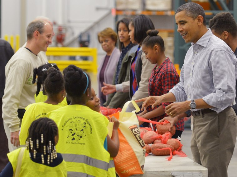 (R to L) US President Barack Obama, daughter Sasha, First Lady Michelle Obama, daughter Malia and mother-in-law Marian Robinson, distribute food at the Capitol Area Food Bank on November 21, 2012, a day ahead of Thanksgiving, in Washington, DC.  (Photo...
