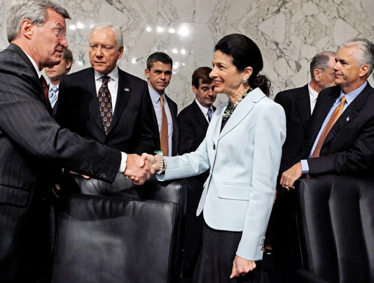 Senate Finance Committee Chairman Max Baucus (D-MT) (L) thanks  Sen. Olympia Snowe (R-ME) for voting in favor of health care reform legislation as committee Republicans Sen. Orrin Hatch (R-UT) and Sen. John Ensign (R-NV) watch, on Capitol Hill October...