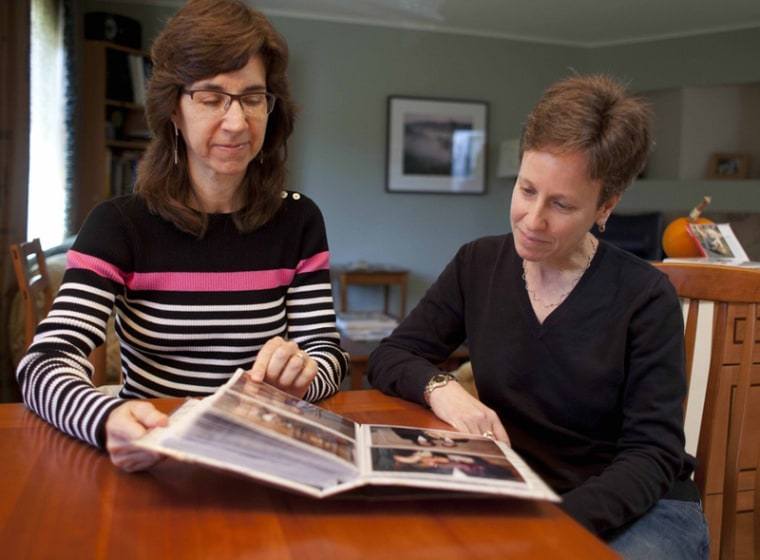 In this photo taken Nov. 12, 2012, Karen Golinski (left) and Amy Cunninghis look over a photo album of their wedding photos in San Francisco. Golinski wanted to enroll her spouse in her employer-sponsored health plan. Four years later, her request...
