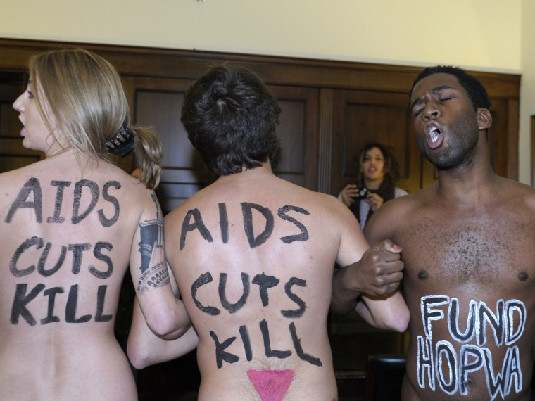 Naked AIDS activists, with painted slogans on their bodies, protested inside the lobby of the Capitol Hill office of House Speaker John Boehner on Tuesday, prior to World AIDS Day. (Susan Walsh/AP Photo)