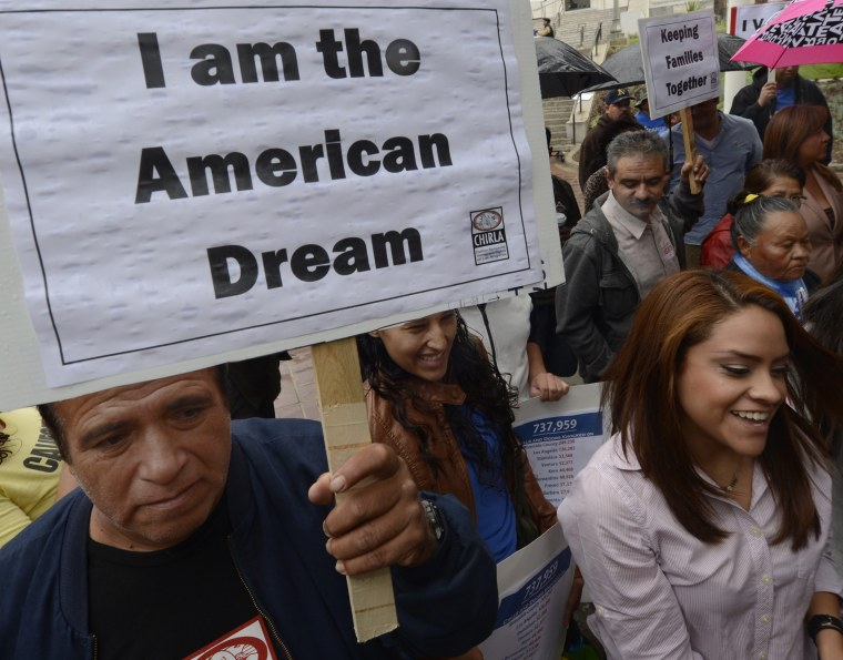 """A man holds a poster that reads """"I am the American Dream"""" as he as he joined other immigrants who gathered in front of L.A. City Hall on Nov. 8, 2012. (Photo by Michael Nelson/EPA)"""