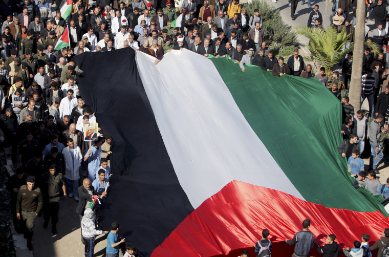 People hold a giant Palestinian flag during a rally in support of the Palestinian UN bid for observer state status, in the West Bank town of Jenin, Thursday, Nov. 29, 2012. The Palestinians are certain to win U.N. recognition as a state on Thursday but...