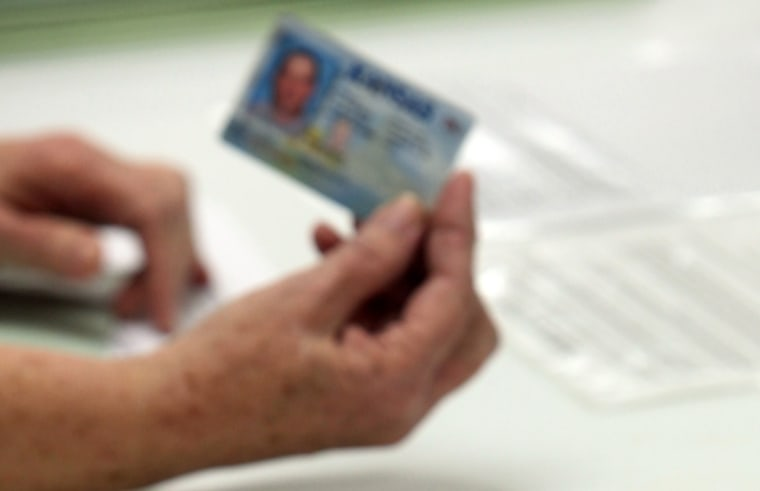 FILE - In this Jan. 10, 2012 file photo, election officials check the photo identification card of a voter in Cimarron, Kan. Voter ID laws designed to deter fraud may end up blocking thousands of legitimate ballots.  (AP Photo/The The Hutchinson News,...