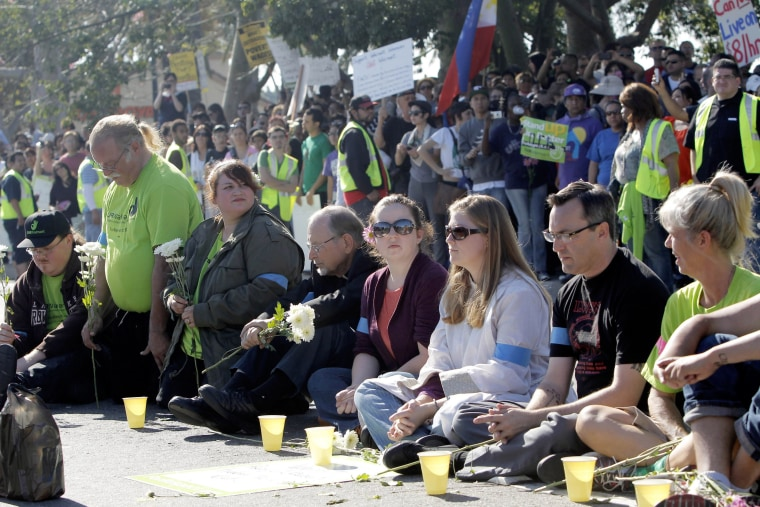 Protestors sit outside the Walmart store Friday Nov. 23, 2012 in Paramount, Calif. Wal-Mart employees and union supporters are taking part in today's nationwide demonstration for better pay and benefits A union-backed group called OUR Walmart, which...