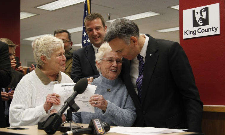 King County Executive Dow Constantine, right, leans down to embrace Pete-e Petersen as her partner, Jane Abbott Lighty, watches after Constantine issued them the first marriage license to a same-sex couples in Seattle. (AP Photo/Elaine Thompson)