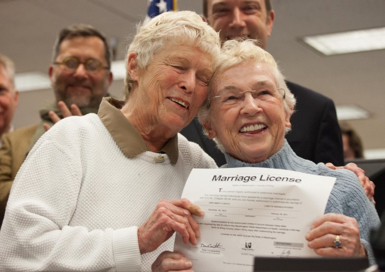 Jane Abbott Lighty, left, and Pete-e Petersen embrace after receiving the first same-sex marriage license in Washington state at the King County Recorder's Office. (Photo by David Ryder/Getty Images)