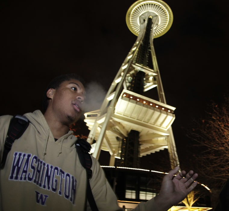 Andre Edwards smokes marijuana, just after midnight at the Space Needle in Seattle. Possession of marijuana became legal in Washington state at midnight, and several hundred people gathered at the Space Needle to smoke and celebrate the occasion, even...