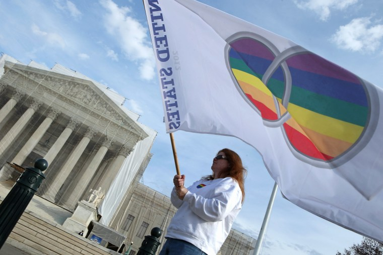 Same-sex marriage proponent Kat McGuckin of Oaklyn, New Jersey, holds a gay marriage pride flag while standing in front of the Supreme Court November 30, 2012 in Washington, DC (Photo by Chip Somodevilla/Getty Images)