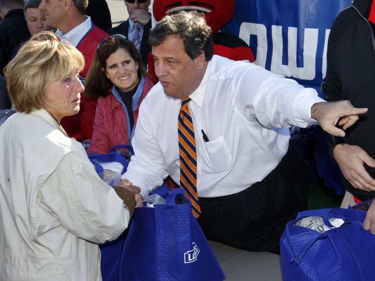 As New Jersey first lady, Mary Pat Christie, center, looks on in Toms River, N.J., Wednesday, Nov. 21, 2012, Gov. Chris Christie tells Nannette Derillo, of Toms River, N.J., to talk to one of his aides about a problem. The Christies joined other...