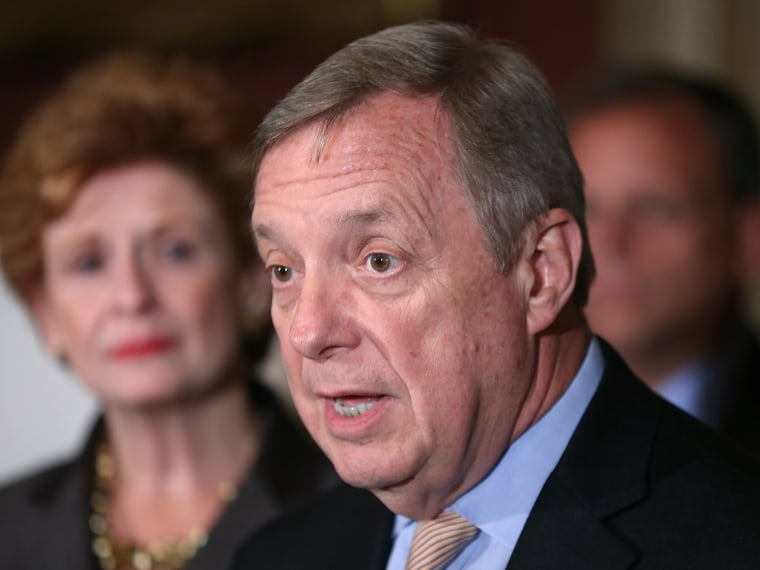"File Photo"" U.S. Sen. Durbin (D-IL) (C) speaks during a news conference while promoting passage of the ""Bring Jobs Home Act"" at the U.S. Capitol as Sen. Debbie Stabenow (D-MI) (L) listens July 18, 2012 in Washington, DC. (Photo by Win McNamee/Getty..."