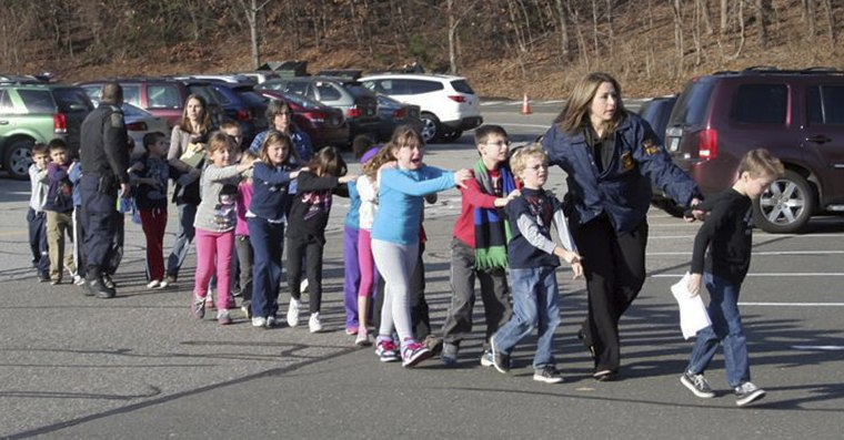 Connecticut State Police lead children from the Sandy Hook Elementary School in Newtown, Conn., following a mass shooting. (Photo by Shannon Hicks/AP Photo)