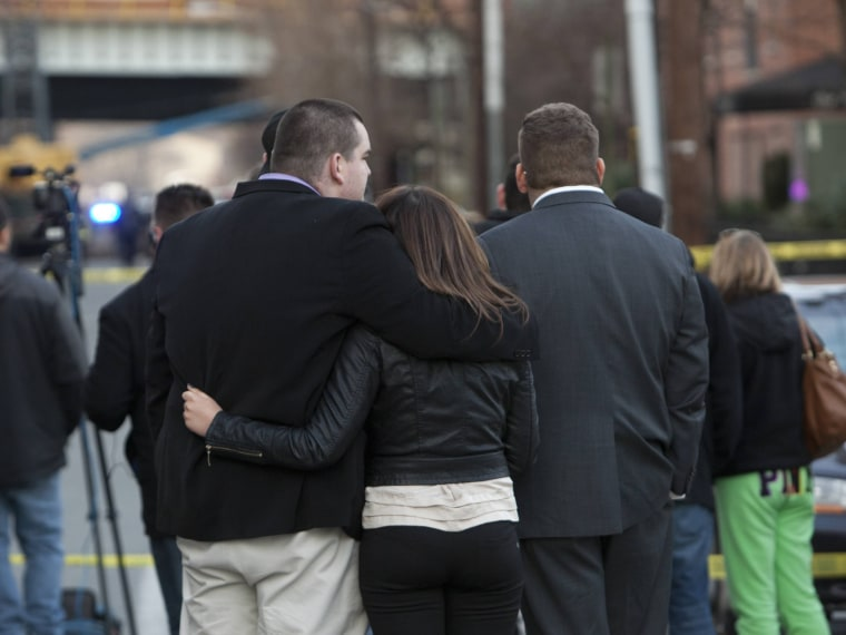 Residents look on where police cordoned off a crime scene related to the shootings at Sandy Hook Elementary School, in Hoboken, New Jersey, December 14, 2012. In Hoboken, New Jersey, police cordoned off a block in connection with the Connecticut...