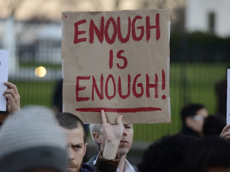A gun control supporter holds up a sign that reads 'Enough is Enough' during a candlelight vigil for victims of the Sandy Hook Elementary School shooting, outside the White House (Photo by Michael Reynolds/EPA)