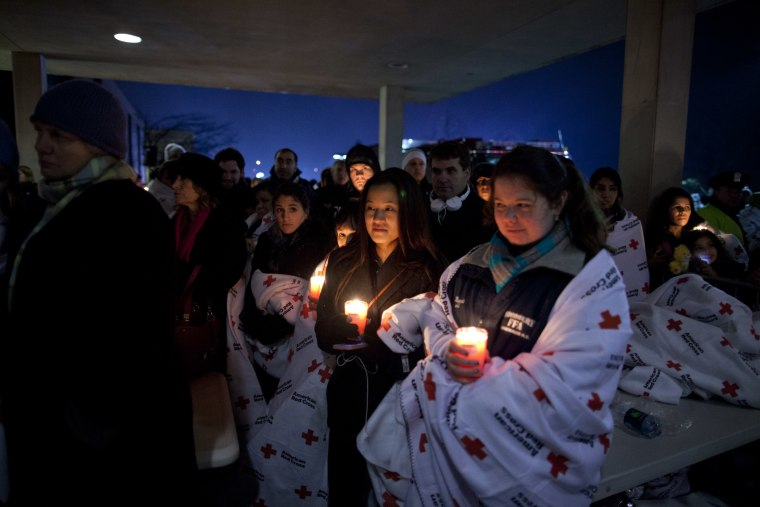 Residents hold a candlelight vigil outside Newtown High School Sunday.(AP Photo/ Evan Vucci)