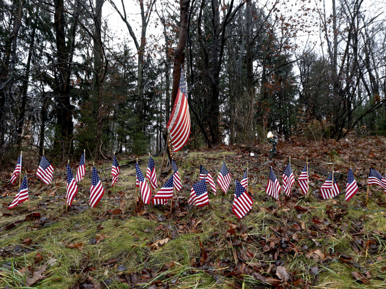 Twenty-seven small U.S. flags adorn a large flag on a makeshift memorial on the side of Highway 84 near the Newtown, Conn., town line as residents mourn victims killed by gunman Adam Lanza, Monday, Dec. 17, 2012. On Friday, authorities say Lanza killed...