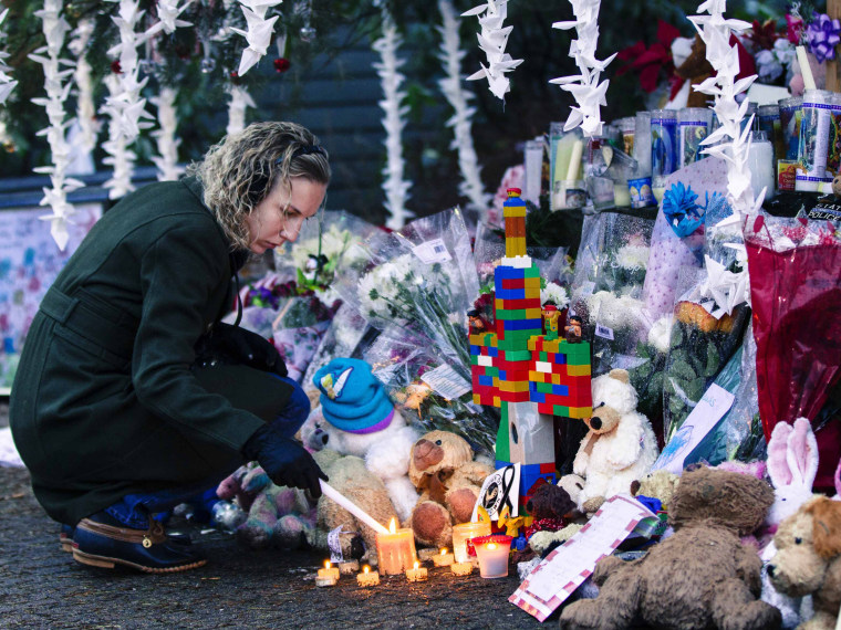 """A woman lights candles while visiting a memorial to the victims of the recent shooting in Sandy Hook Village in Newtown, Connecticut December 17, 2012. The small Connecticut town shattered by an act President Barack Obama called \""""unconscionable evil,\""""..."""
