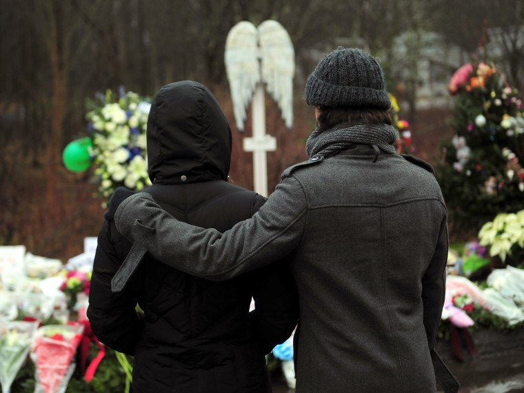 People pay their respects at a makeshift shrine to the victims of an elementary school shooting in Newtown, Connecticut, December 17, 2012. Funerals began Monday in the little Connecticut town of Newtown after the school massacre that took the lives of...