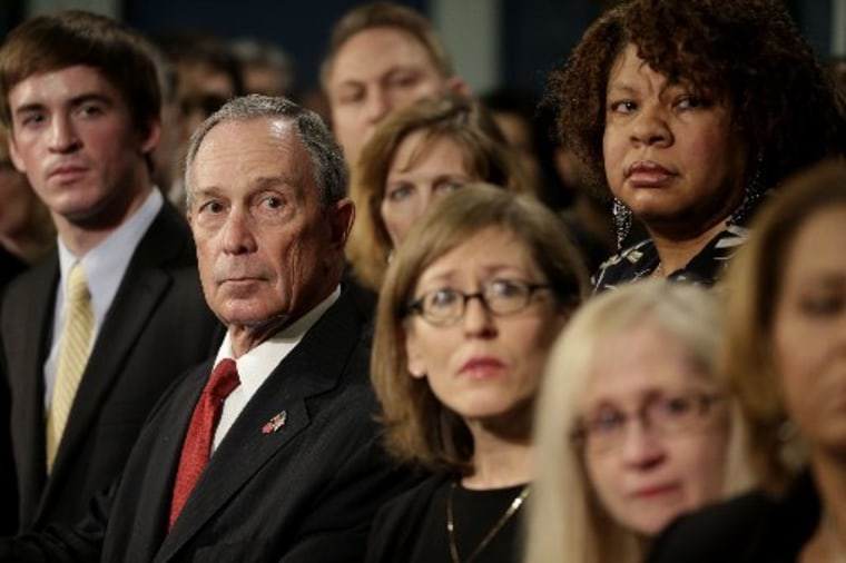 New York City Mayor Michael Bloomberg, second from left, watches a video testimonial surrounded by shooting survivors and victims' relatives during a news conference in City Hall in New York, Monday, Dec. 17, 2012.  Bloomberg and dozens of shooting...