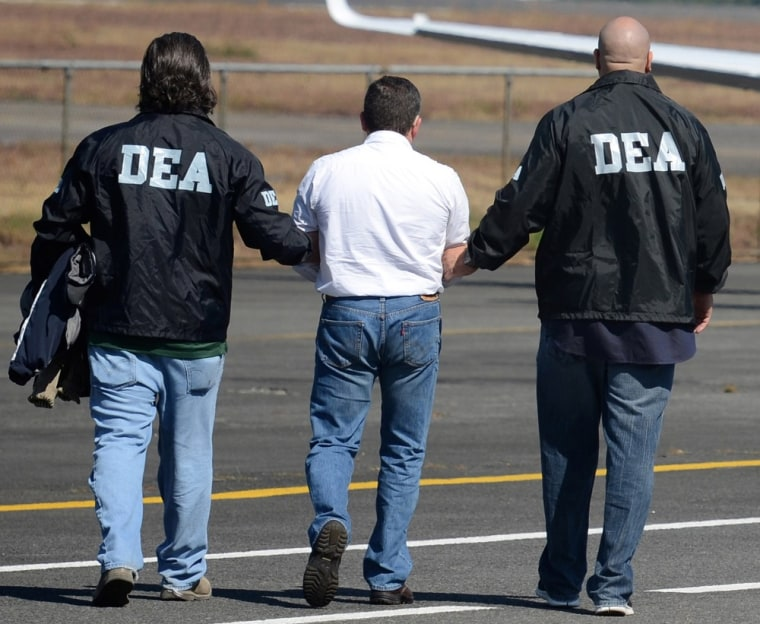 Adrug trafficker Horst Walther Overdick is escorted by DEA agents to a waiting plane during his extradition to the U.S., at an air force base in Guatemala City, Monday Dec. 10, 2012. (AP Photo/Guatemalan U.S. Embassy)