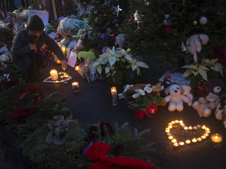 A woman lights candles at a memorial for victims of the Sandy Hook Elementary shooting near the school in Sandy Hook Village in Newtown, Connecticut.  (Photo by Adrees Latif/Reuters)
