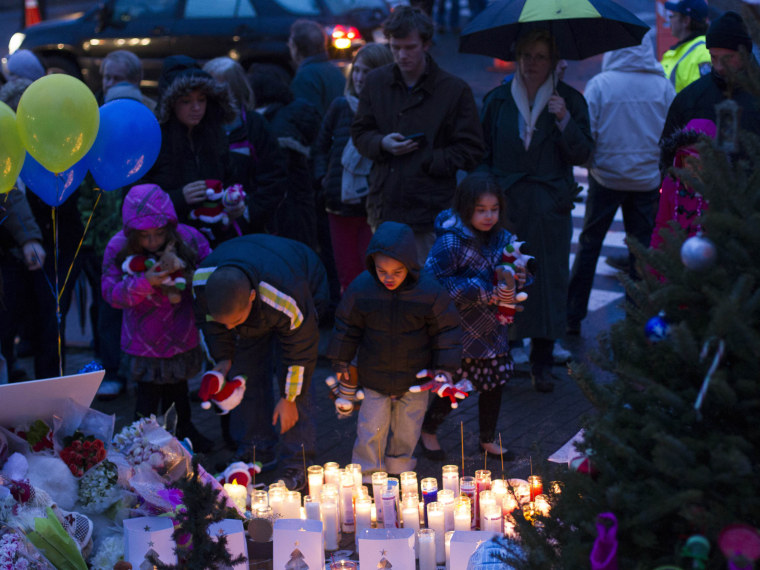 Mourners place candles and stuffed toy animals on a memorial for victims of the recent mass shooting in Newtown, Connecticut December 16, 2012. (Photo by Lucas Jackson/Reuters)
