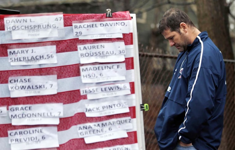 A man in Newtown, Connecticut, pays his respect to the victims killed at Sandy Hook Elementary School. (Julio Cortez / AP)