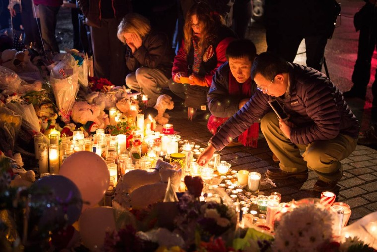 Zong Yang Tan, right, and Guan Fu Jiang light candles at the makeshift memorial in the center of Sandy Hook village on Monday in Newtown, Conn. (David Friedman / NBC News)
