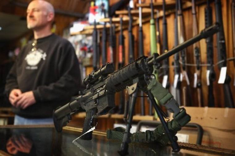 An AR-15 style rifle sits on the counter by Craig Marshall as he assists a customer at Freddie Bear Sports sporting goods store on December 17, 2012 in Tinley Park, Illinois. (Photo by Scott Olson/Getty Images)