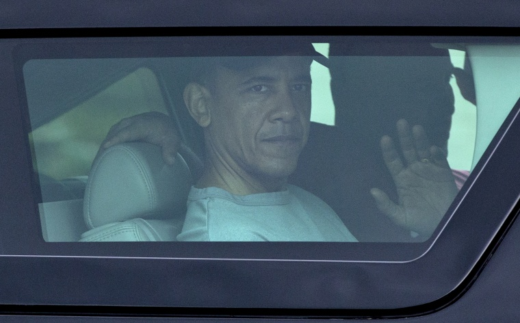 President Barack Obama waves from the window of his motorcade vehicle as he returns from a workout at Marine Corp Base Hawai. The president and the first family are in Hawaii for a family holiday vacation. (Photo by Carolyn Kaster/AP)